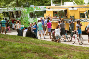 ATLANTA, GA - APRIL 2016: A large crowd of people buy meals from food trucks lined up in Grant Park at the Food-o-rama festival in Atlanta GA on April 16 2016 .