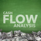 Cash flow analysis on green blackboard with dollar bills