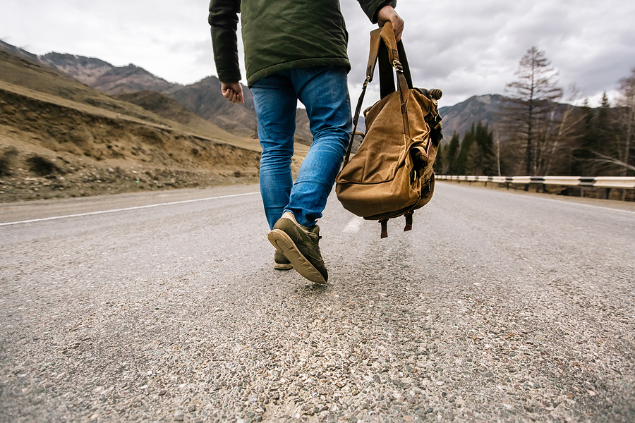 Man with backpack walking down road; business journey concept