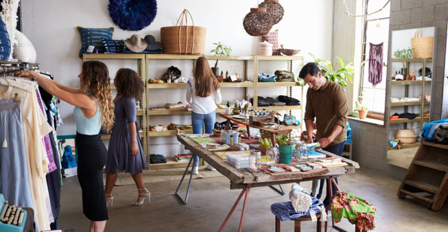 Customers and staff in a busy boutique; small business sale concept