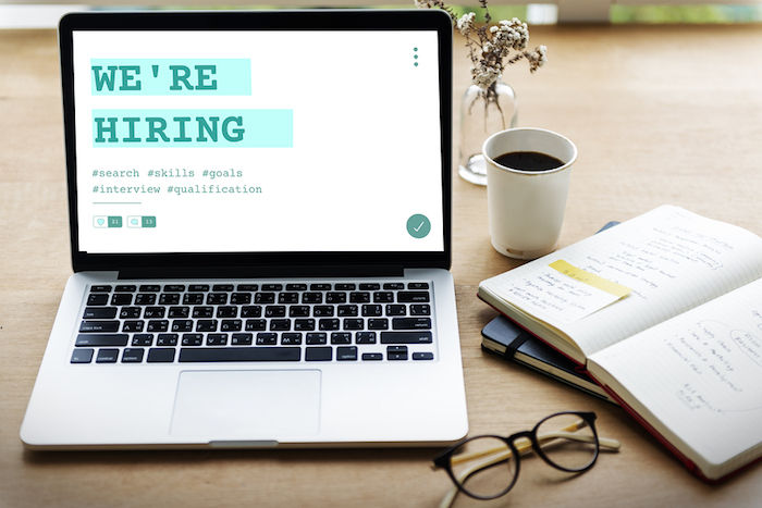 "Hiring via your business website; laptop on desk with text reading ""we're hiring"""