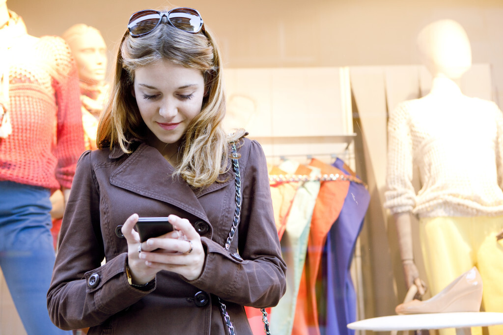 Girl on smartphone in front of clothing store
