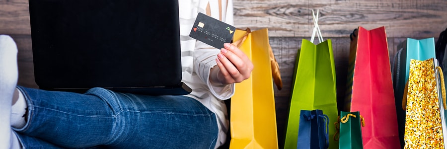 Woman sitting with laptop and colorful gift bags shopping online