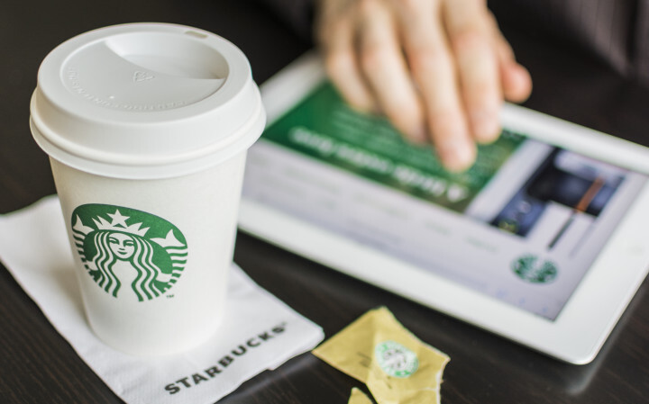 An entrepreneur views information about Starbucks on his tablet while drinking coffee