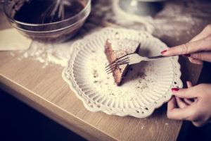 Dark chocolate cake with icing powdered sugar on top served on a cute little vintage ceramic plate.Homemade chocolate cake served with mess in the background of making the cake.Calories and sugars