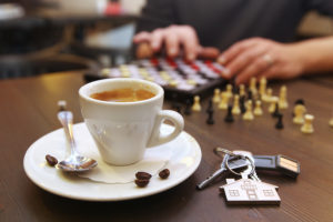 Cup of coffee and chess on the desk
