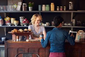 Customer In Coffee Shop Ordering Using Digital Tablet
