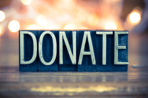 The word DONATE written in vintage metal letterpress type on a soft backlit background.