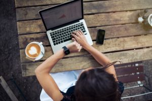 Overhead view of young woman checking time on her smartwatch while working on her laptop at a cafe. Top view shot of female sitting at a table with a cup of coffee laptop and mobile phone.