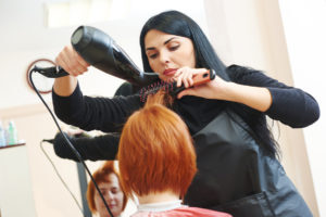 hairdresser drying hair with blow dryer of woman client at beaut