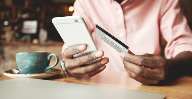 Man on cell phone holding credit card; SaaS pricing concept