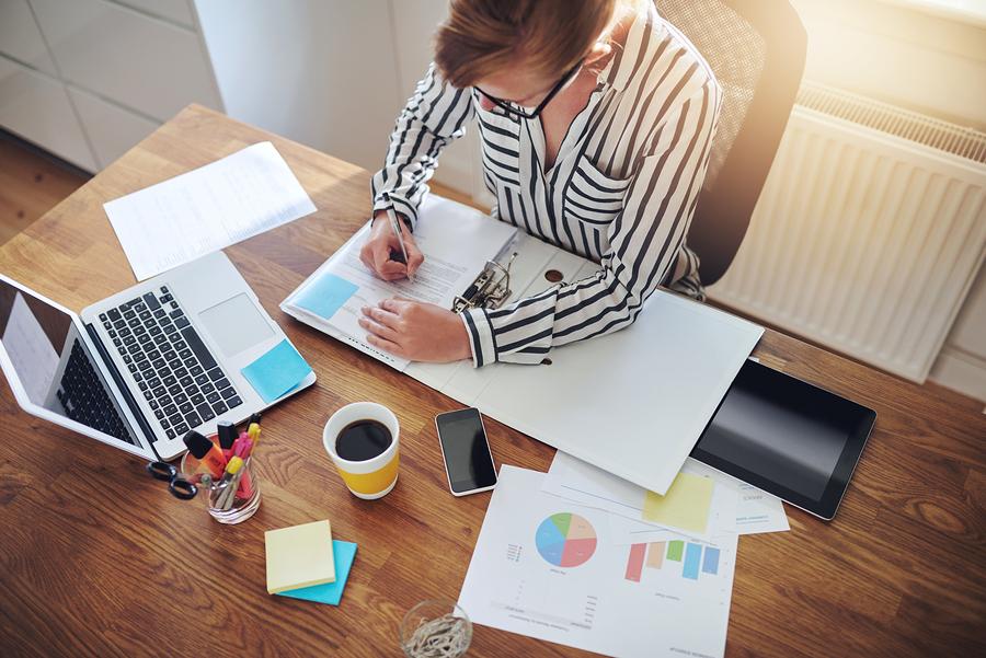 entrepreneur working on business analytics at her desk; marketing ROI concept