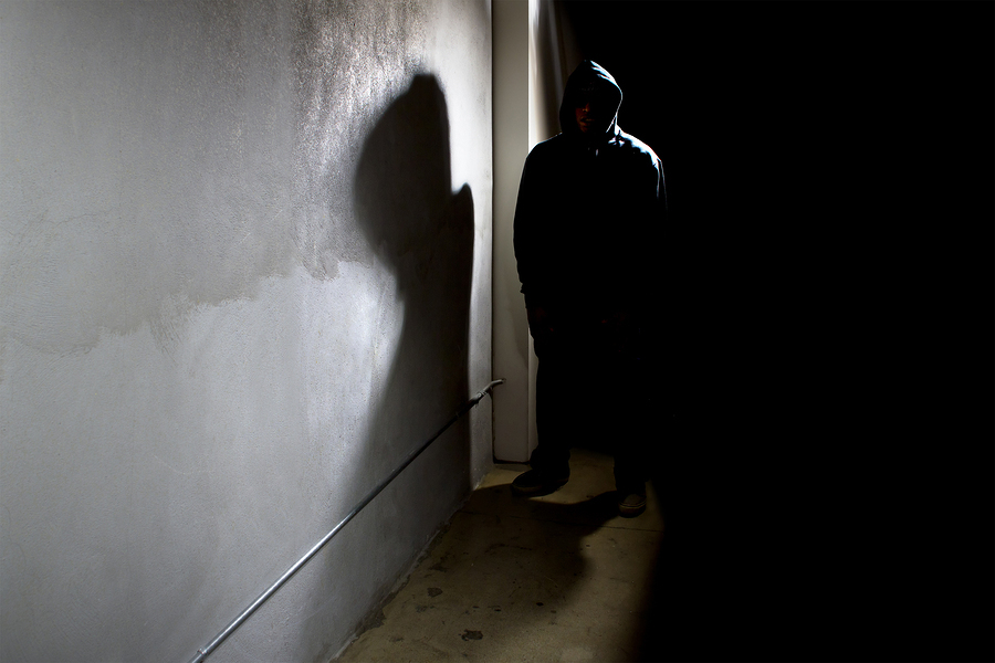 Hooded figure in alley; cyber security, small business