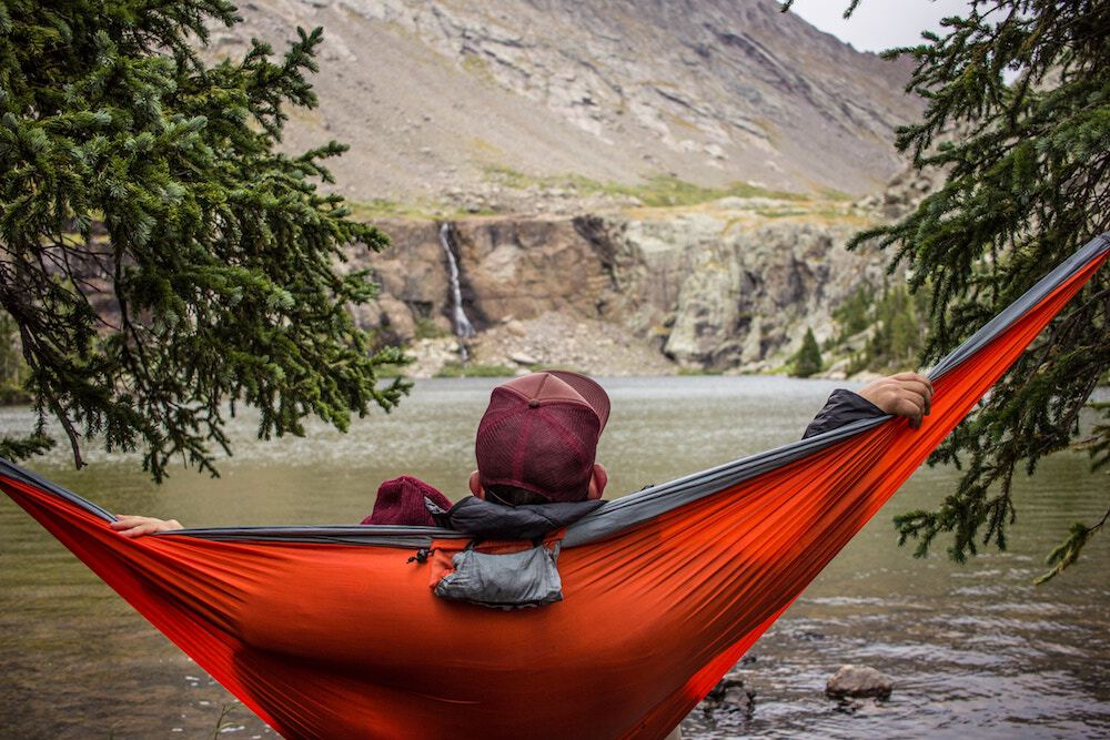 Man relaxing in a hammock while camping; work life balance concept