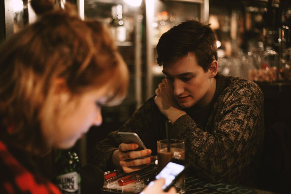 Young man using cell phone; voice search tips