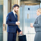 Business man and woman waiting for an elevator; elevator speech concept